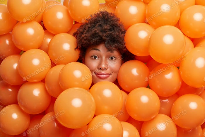 Photo of attractive curly haired woman surrounded by inflated balloons smiles gently poses at camera