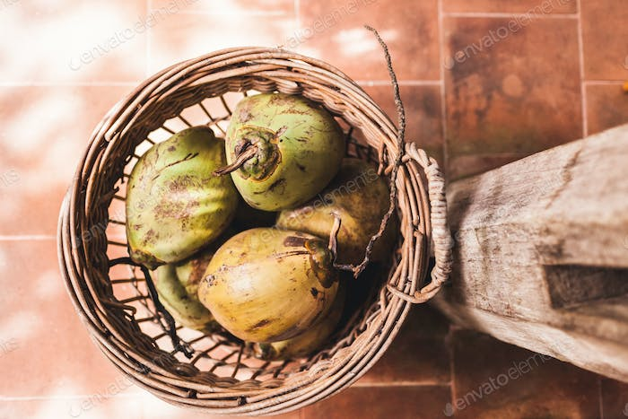 Wicker basket with fresh green young coconuts. View from above