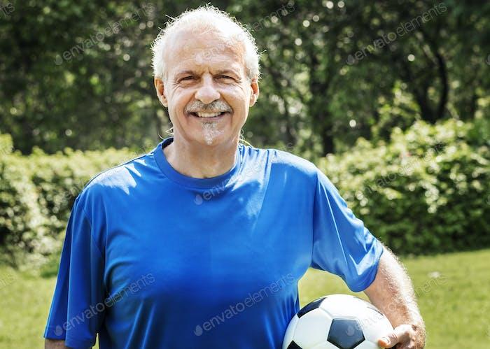 Mature man holding a football