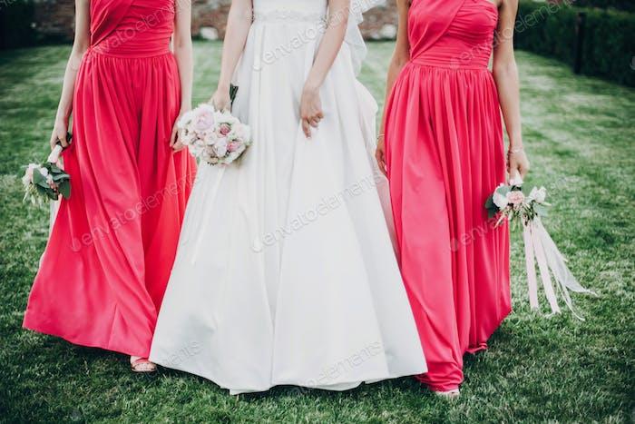 Maravillosa novia caminando con damas de honor en vestidos de color rosa