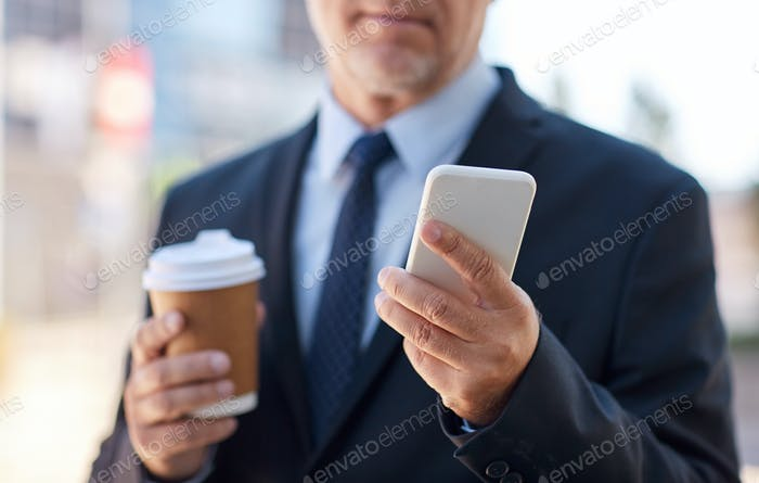 senior businessman with smartphone and coffee