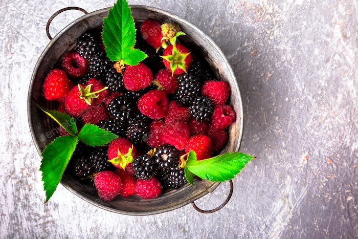 Blackberry and raspberry in a metal bowl on grey wooden background. Top view.