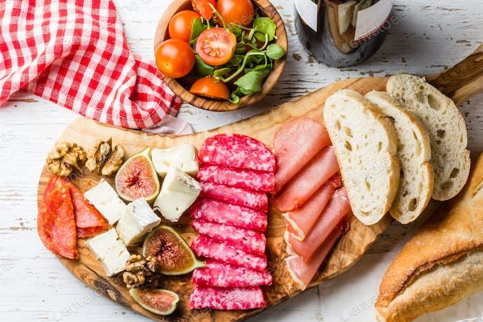 Antipasto. Olive board with salami, ham serrano, cheese, nuts and ciabatta bread