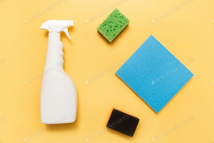 White plastic hand spray bottle with sponges on yellow background