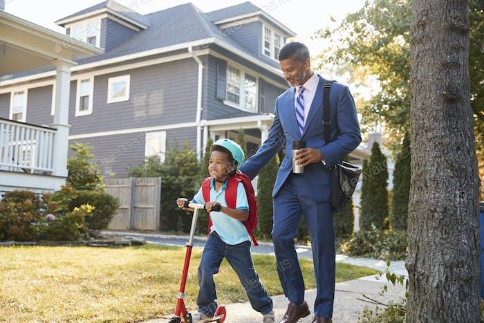 Geschäftsmann Vater Walking Sohn auf Roller zur Schule