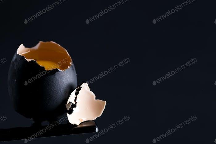 Schwarzes zerbrochenes rohes Ei mit frischem gelbem Eigelb auf dem gleichen Farbhintergrund