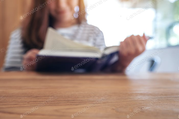 Closeup image of a beautiful asian woman holding and reading a book
