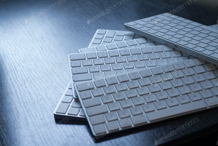 closeup of computer keyboards on a black dark desk