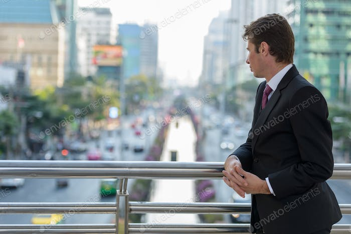 Businessman looking at the streets and thinking on footbridge at