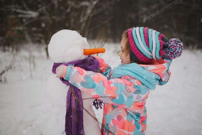 Mädchen macht Schneemann im Winterpark