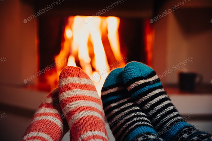 Feet in wool striped socks by the fireplace. Relaxing at Christmas fireplace on holiday evening.