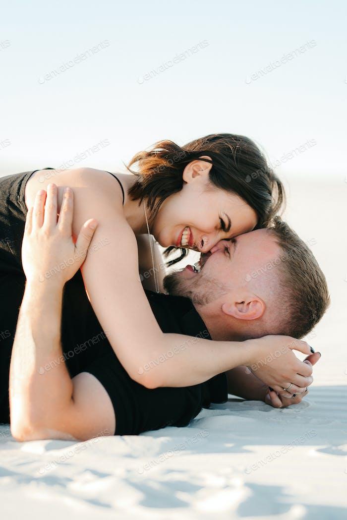 junges Paar ein Mann und ein Mädchen mit freudigen Emotionen in schwarzen Kleidern gehen durch die weiße Wüste