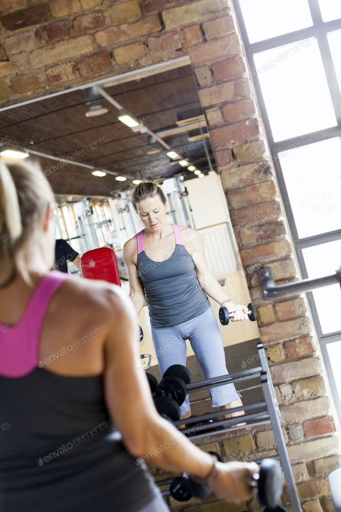 Mature woman lifting weights in front of mirror at health club