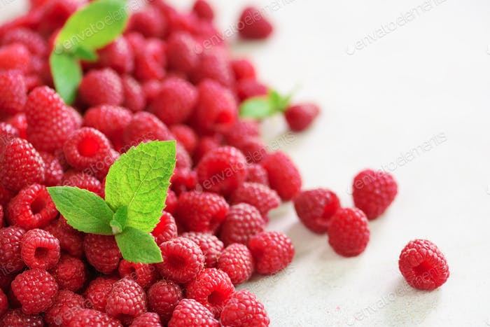 Fresh organic raspberries with mint leaves. Fruit background with copy space. Summer and berries