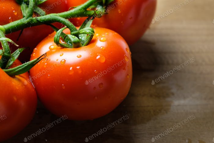 Tomatoes panicles on a wooden chopping board