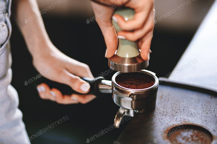 A young pretty slim girl,wearing casual outfit,is cooking coffee in a modern coffee shop. It focuses