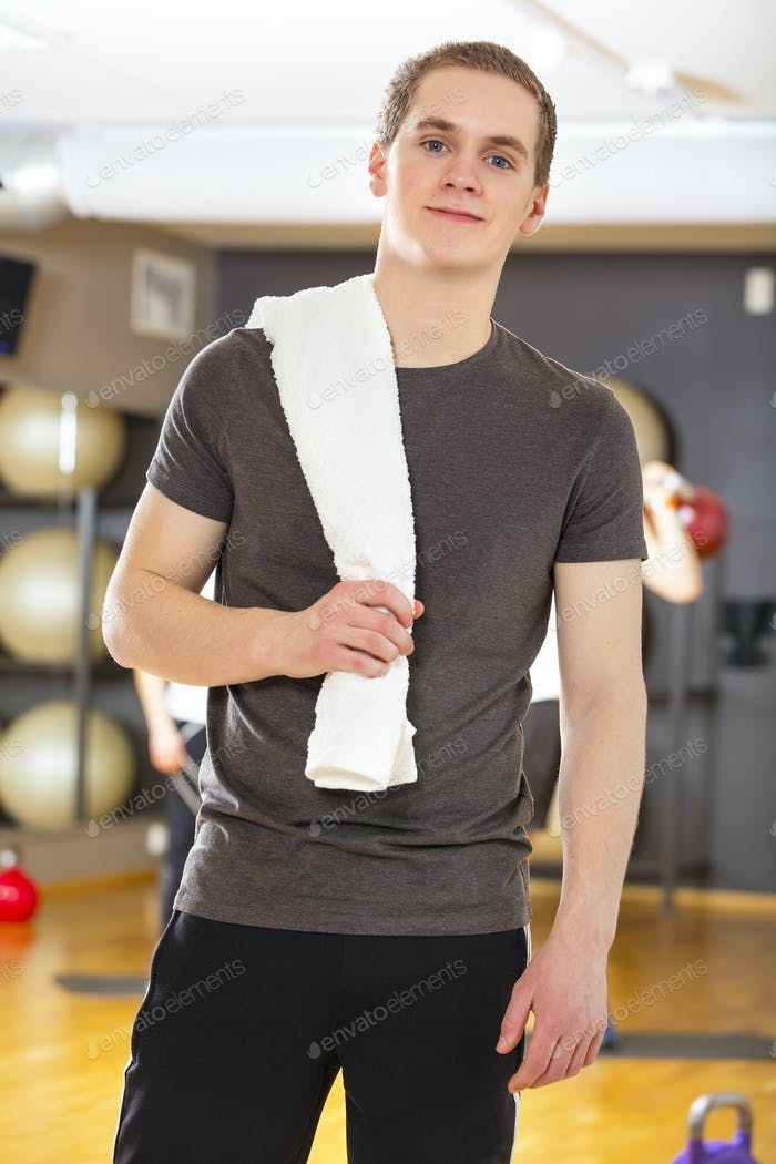 Confident and smiling young man exercising at fitness gym