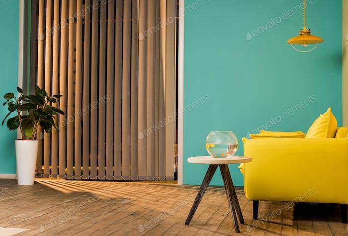 gelbes Sofa und Aquarium mit Fischen auf dem Tisch im Wohnzimmer
