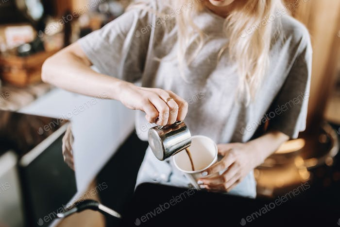 A pretty thin blonde girl with long hair, dressed in casual outfit, pours coffee into a glass in a