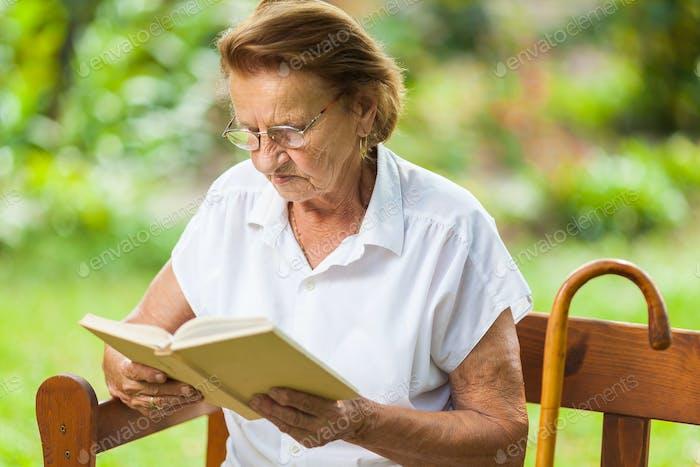 Ältere Frau sitzt und entspannt auf einer Bank im Park
