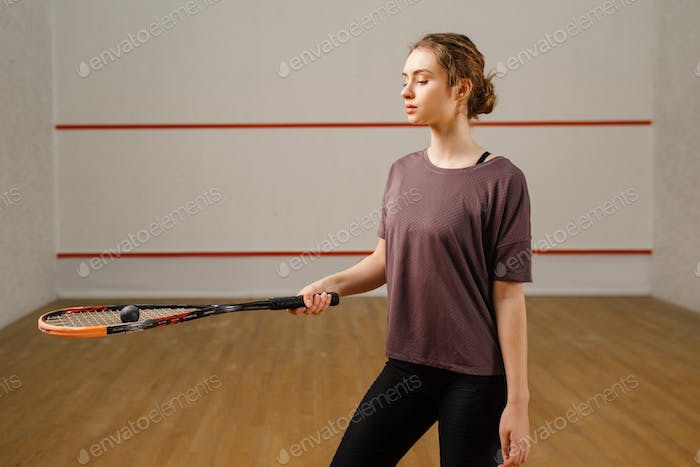 Female player with squash racket and ball on court