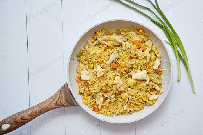 Köstlicher gebratener Reis mit Huhn und Gemüse in der Pfanne serviert. Auf weißem Holztisch platziert