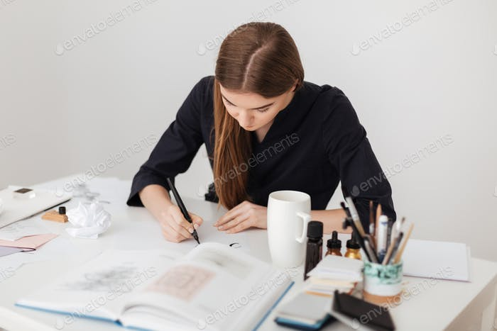 Portrait of young beautiful lady sitting at the white desk and writing notes on paper with open book