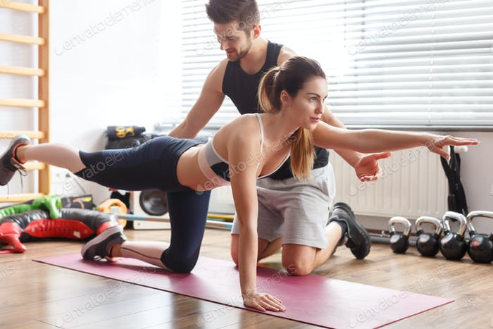 Trainer helping woman during exercise