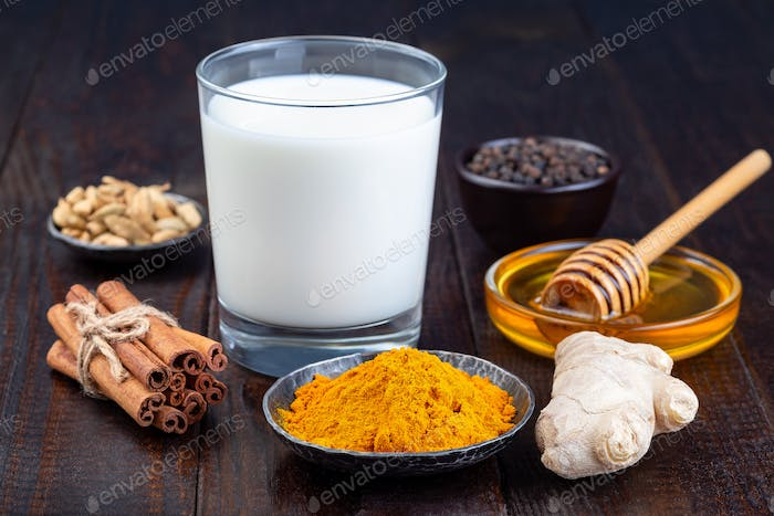 Ingredients for turmeric moon milk on  wooden background, horizontal