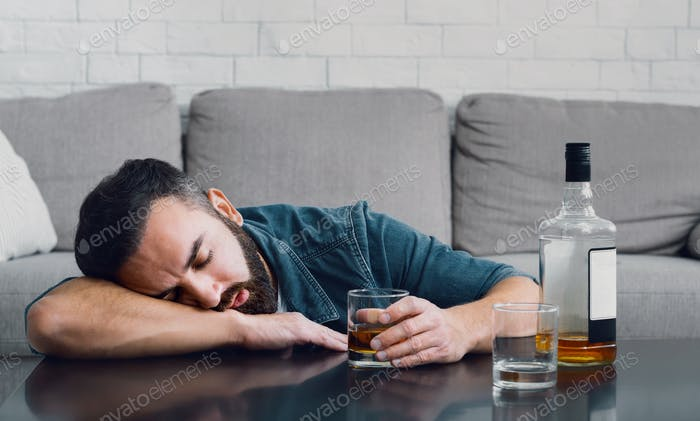 Alcohol addiction. Drunk man sleeping leaning on table with bottle and glass
