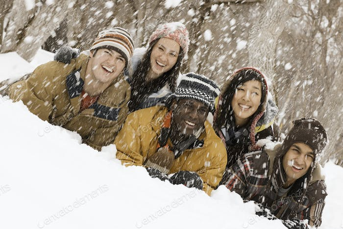 Five young people lying on the snow laughing. Snow falling.
