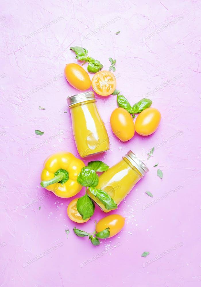 Yellow vegetable vegan juice on pink background