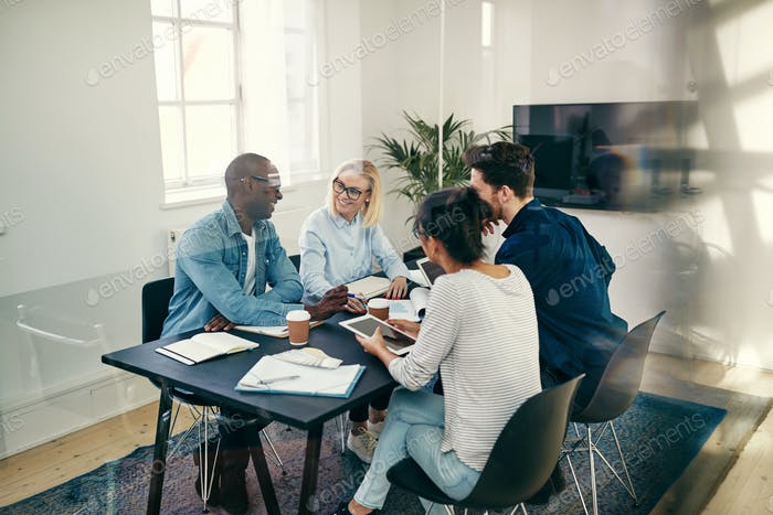 Smiling group of businesspeople talking together in an office boardroom