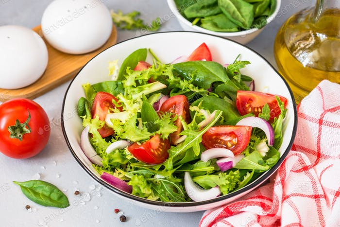 Green salad from fresh leaves and tomatoes