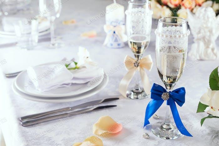 edding Champagnergläser auf weißer Tischdecke mit Tischeinstellung auf weiß, Nahaufnahme