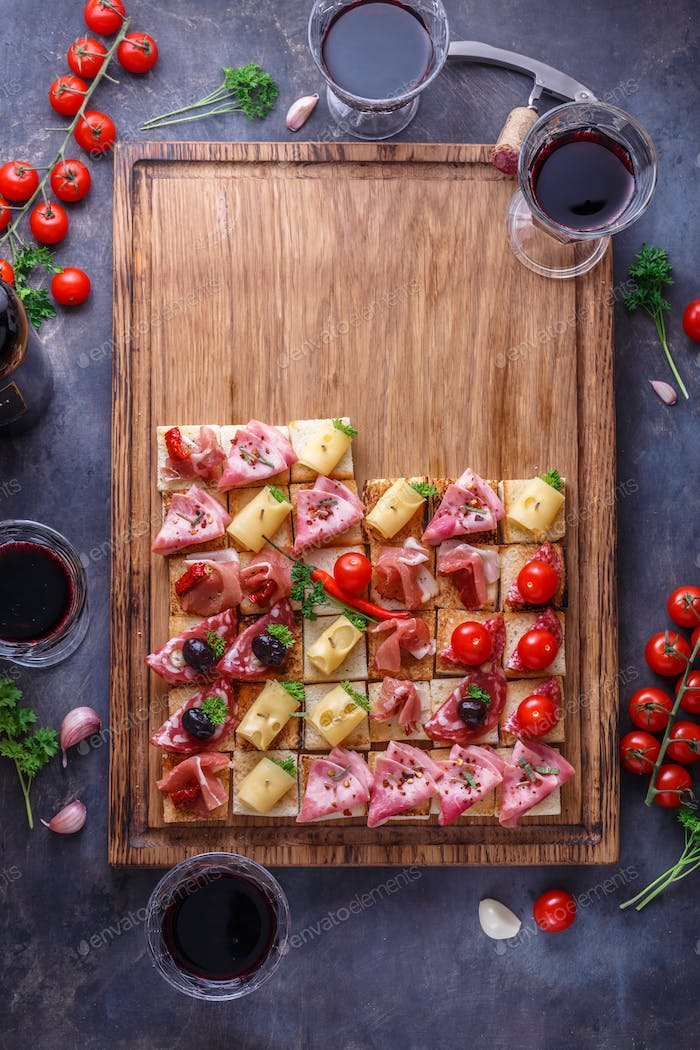 Tasty Italian appetizers, or bruschetta, slices of toasted baguette topped with ham, prosciutto