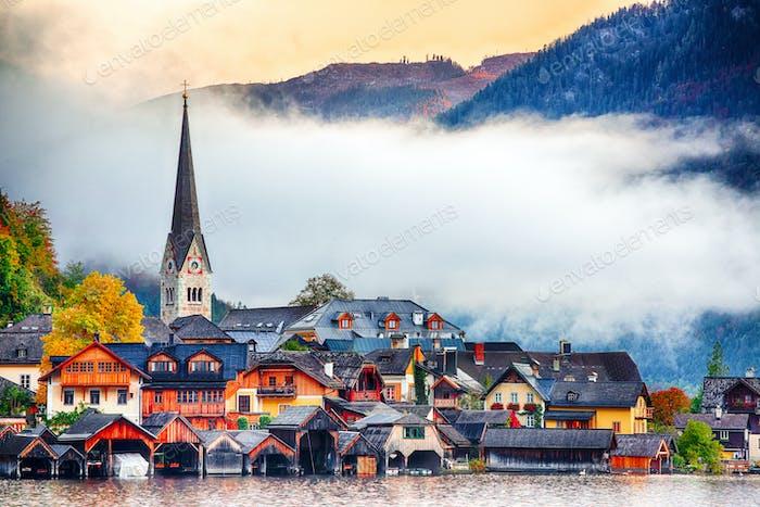 famous Hallstatt mountain village with Hallstatter lake. Foggy autumn sunrise on Hallstatt lake