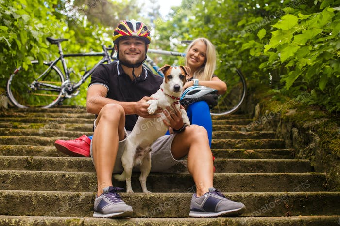 Couple of cyclists with their dog.