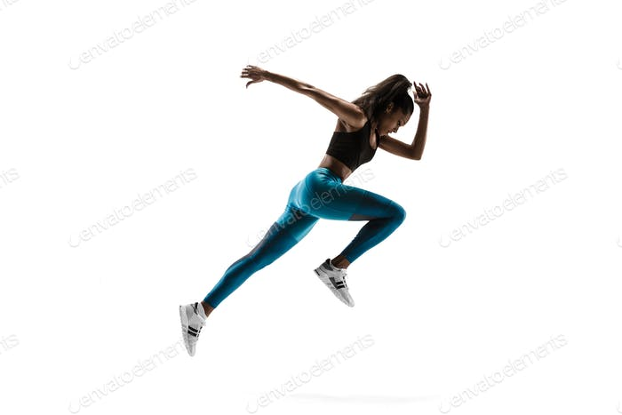 Young african woman running or jogging isolated on white studio background.