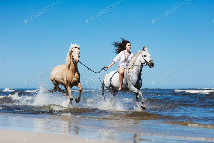 Girl galopading through the sea with two horses.