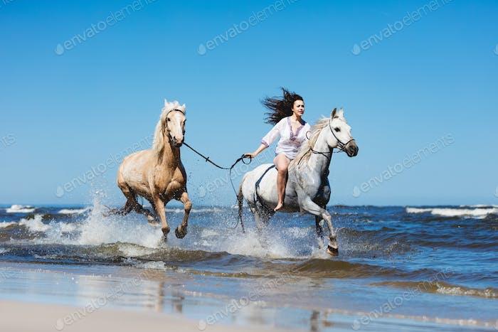 Mädchen Galopading durch das Meer mit zwei Pferden.