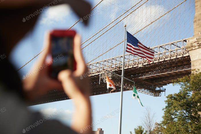 Tourist Taking Photo Of Brooklyn Bridge On Mobile Phone