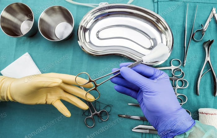 Surgeon working in operating room, hands with gloves holding scissors of suture and torundas