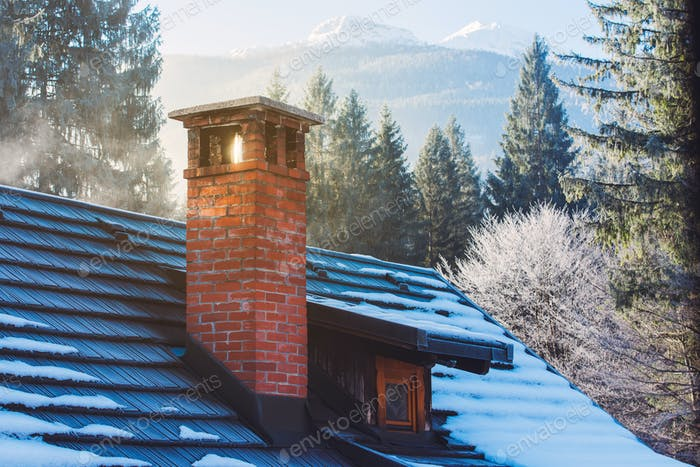 Mountain cottage chimney in winter