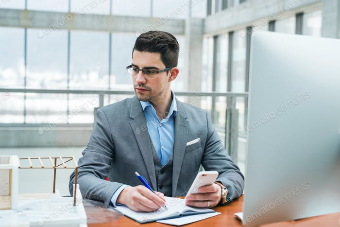 Young businessman or architect with computer and smartphone in office, working.