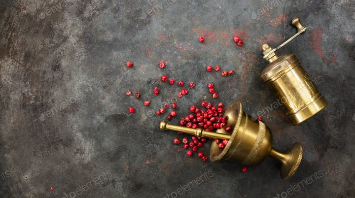 Pink peppercorns, a bronze pepper mill and a mortar on metal rusty background, top view, copy space