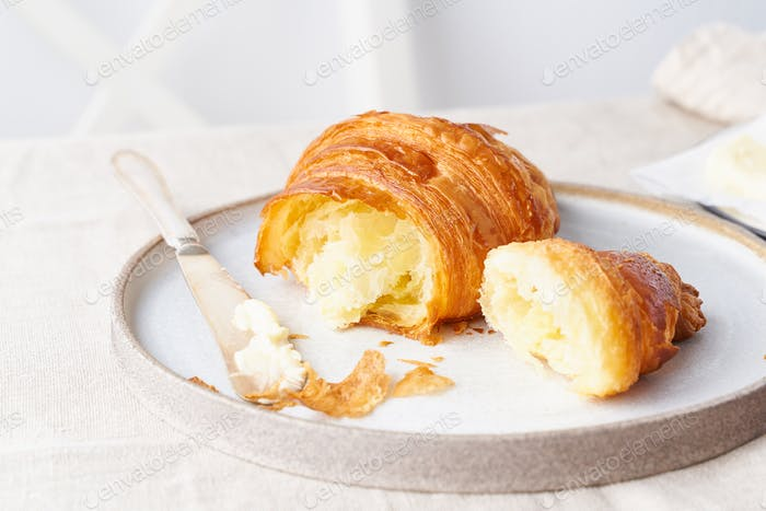 Coffee with croissant. Bright sunny morning, leisurely breakfast with fresh pastries, side view