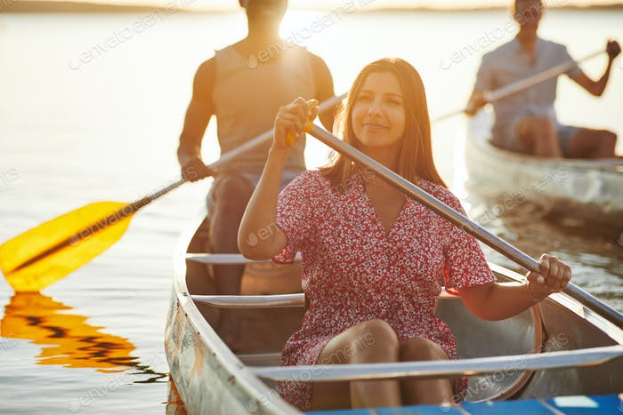 Smiling young woman canoeing with friends on a lake