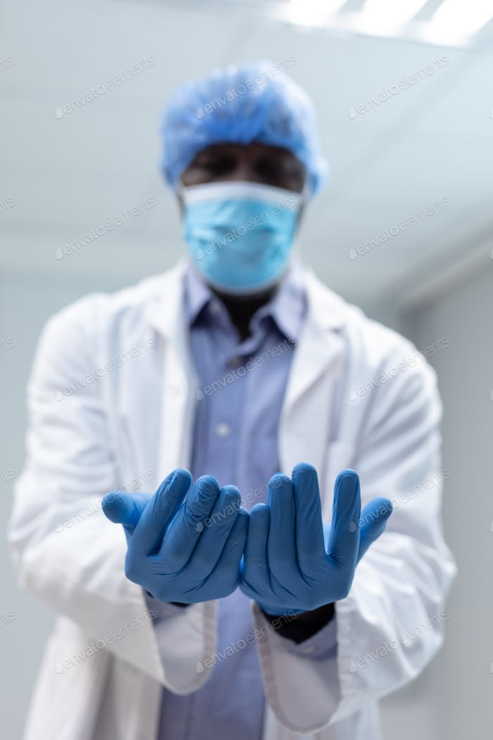 Portrait of african american male doctor wearing face mask surgical cap and latex gloves