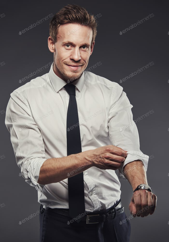 Handsome businessman rolling up his sleeves